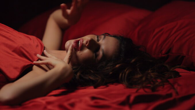 Seductive woman lying on red satin cloth in bed.