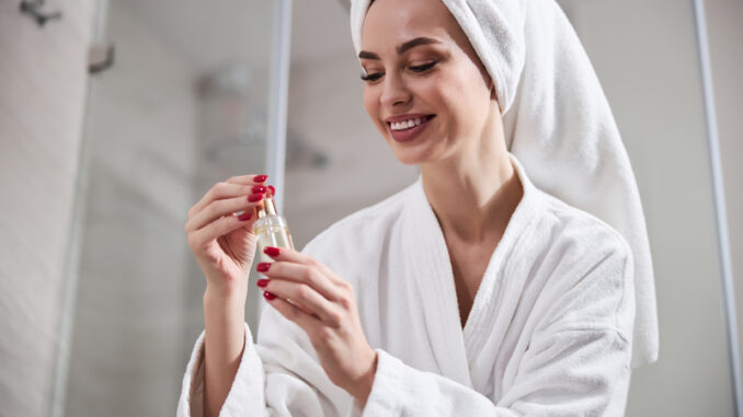 Excited young woman wearing bathrobe and towel on her head holding and looking at small bottle with cosmetic product