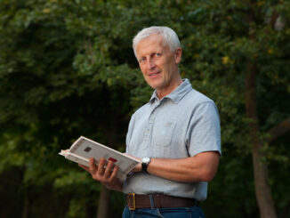Skinny happy old man reading book in the park outdoor