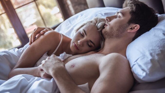 Beautiful young couple is hugging while sleeping in bed at home