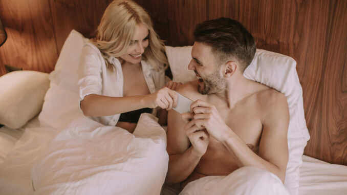 Happy couple in bed at home and use mobile phone