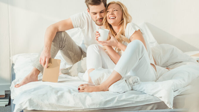 young happy couple drinking coffee in bed at morning