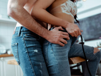 Cropped view of young couple in jeans kitchen