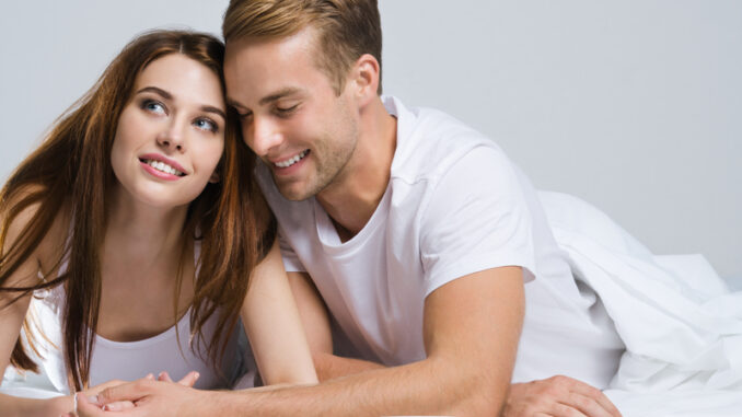 Portrait of young attractive happy couple on the bed at bedroom.