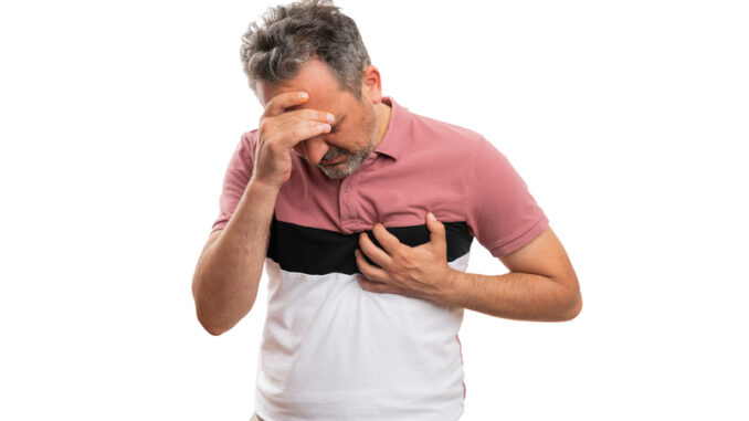 Adult man in colourful fashionable modern summer attire touching chest and head making migraine heart-attack gesture as healthcare