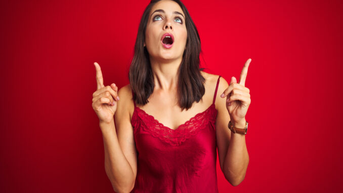 Young beautiful woman wearing lingerie over red isolated background amazed and surprised looking up and pointing with fingers and raised arms
