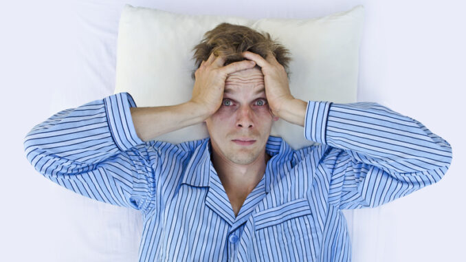 Stressed man waking up scared/worried or not able to get to sleep