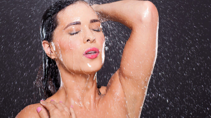 young woman in shower over black background