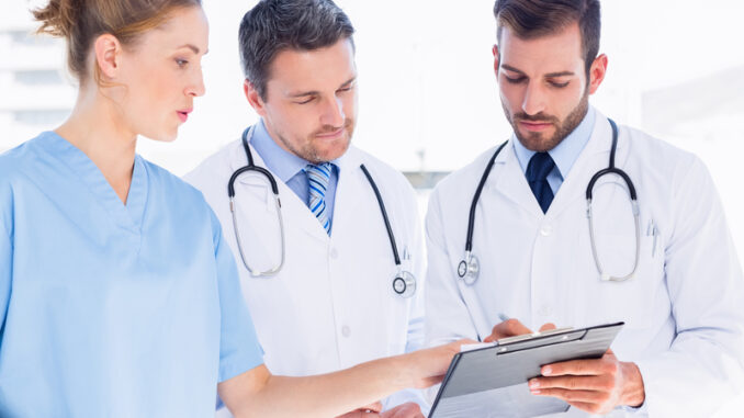 Two male doctors and female surgeon reading medical reports at the hospital