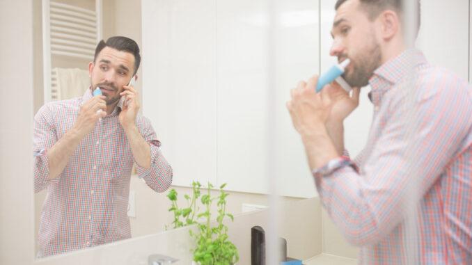 Man standing in bathroom, brushing teeth and having phone call.
