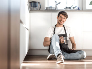 Young man with a glass of water sitting on the floor in the home kitchen.