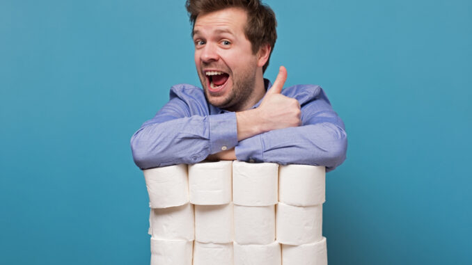 Excited happy caucasian man holding a pile of toilet paper showing thumb up isolated on blue background.