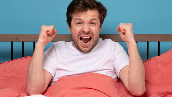 Caucasian positive man holding fists up resting at his bed at home