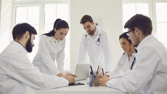 Group of doctors talking sitting at a table in the office of the hospital.