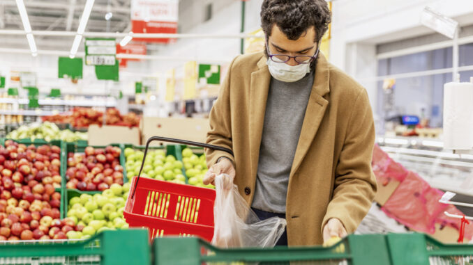 A young man in a medical mask is choosing fruits in a large supermarket.