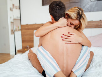 Couple in love lying on bed and touching each other tenderly