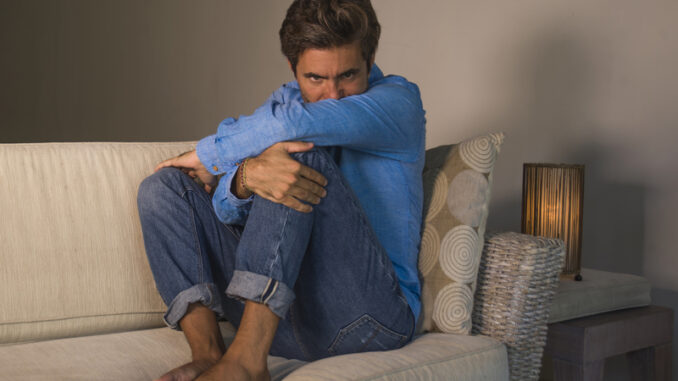 Lifestyle portrait of young attractive and handsome sad latin man sitting tired