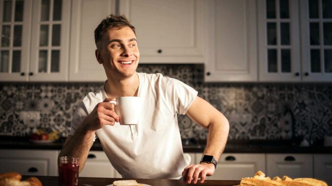 Handsome man drinking coffee at home in the kitchen