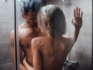 nude heterosexual couple looking at each other, embracing and taking shower together