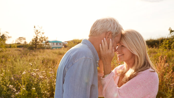 Loving Mature Couple In Countryside Head To Head Against Flaring Sun