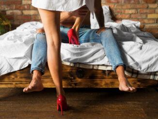 Seductive women wearing red high heel shoes in bedroom