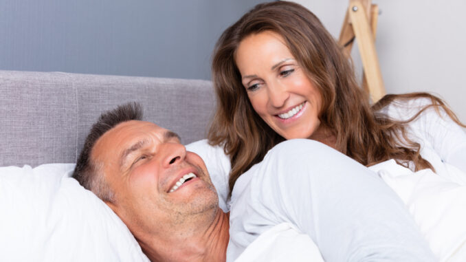 Loving Mature Couple Lying On Bed And Looking At Each Other