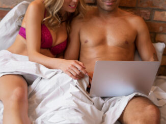 Couple looking at laptop together in bedroom