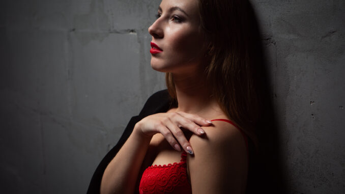 A young woman in red underwear and a man`s jacket draped over her shoulders