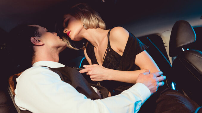 Handsome stylish men embracing fashionable young women in car