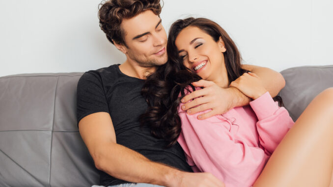 Selective focus of smiling woman touching boyfriend on sofa on grey