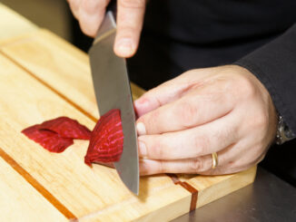 Professional chef cutting beet-root on wooden plank