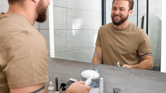 Bearded Male Person Brushing Teeth Using Electric Toothbrush