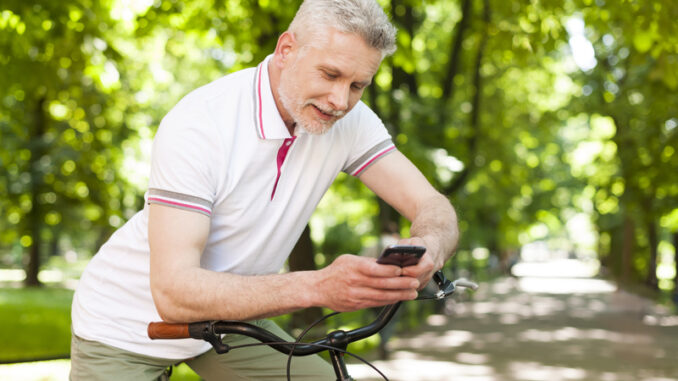 Mature smiling man using contemporary mobile phone at park