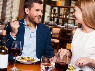 Beautiful young loving couple enjoying dinner at the restaurant