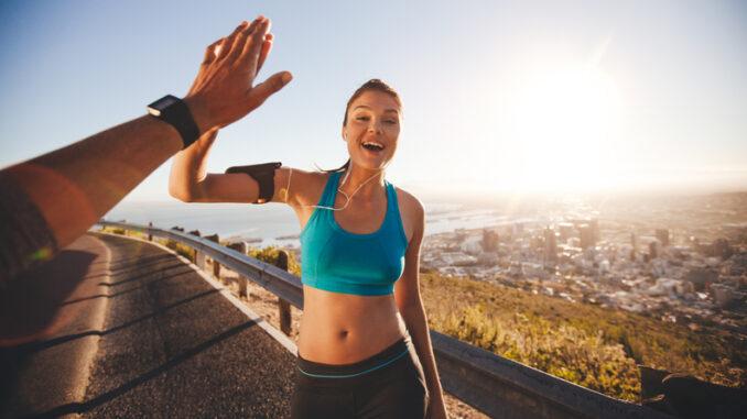 Fit young women high fiving her boyfriend after a run.