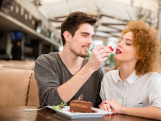 Portrait of a beautiful couple eating cake with strawberry in restaurant