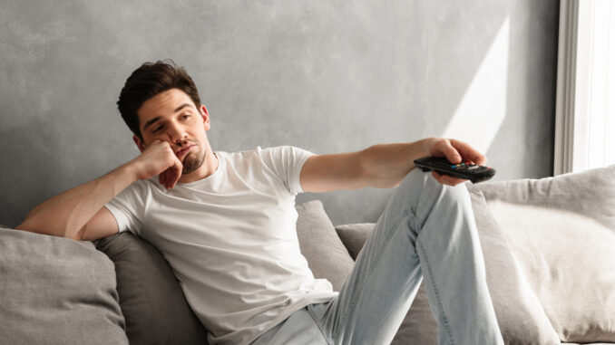 Photo of young bored man sitting on couch at home and changing TV channels with disinterest