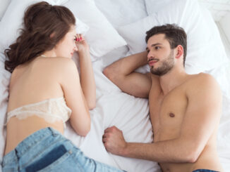 young couple resting on bed together at home