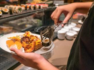 Man hand choosing sushi, lobster in the luxury buffet