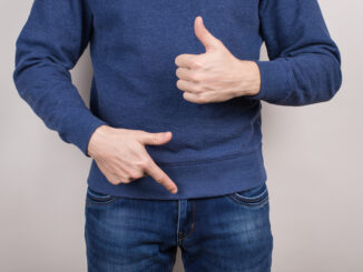 Cropped close-up photo of satisfied confident cool guy demonstrating pointing on his he organ in pants trousers isolated grey background.