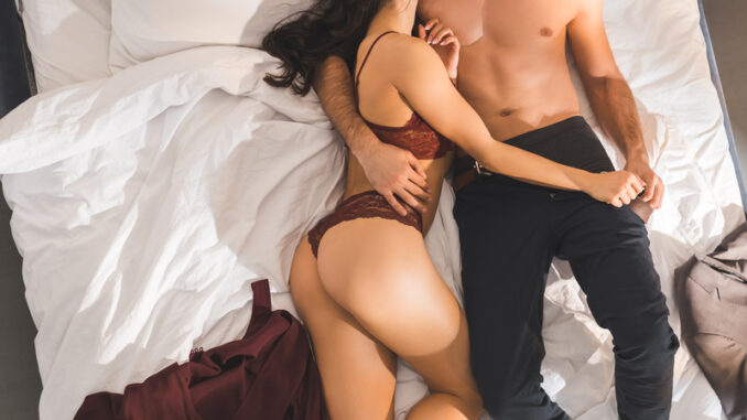 Partial view of woman in red lingerie lying with man in bed
