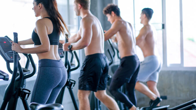 Beautiful sport women exercise with elliptical machine among the other men in the gym with day light