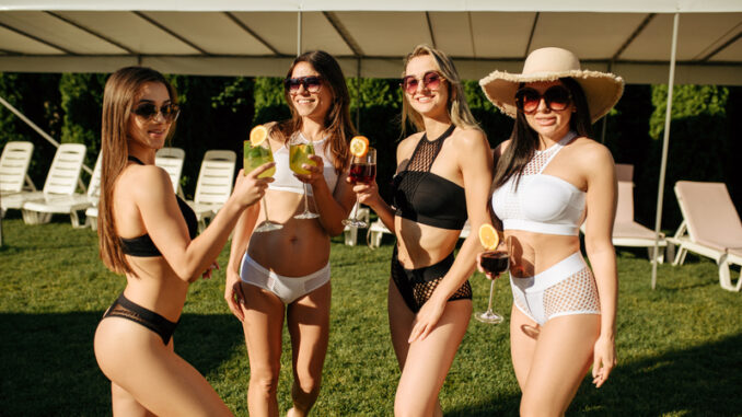 women in swimsuits poses with fresh coctails