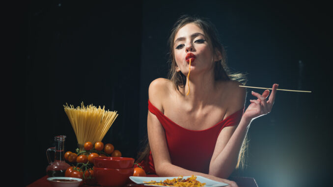 Young woman eating tasty pasta on black
