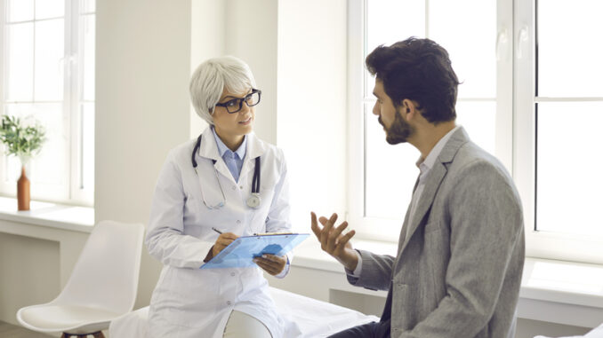 Worried man talking to doctor while sitting in exam room during consultation in modern clinic or hospital.