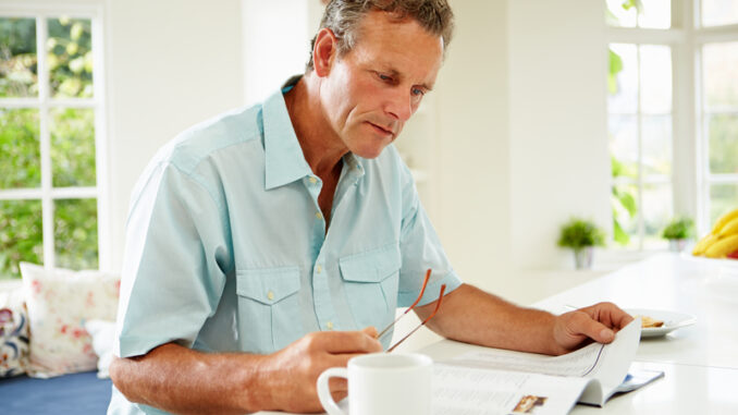 Middle Aged Man Reading Magazine Over Breakfast At Home Concentrating