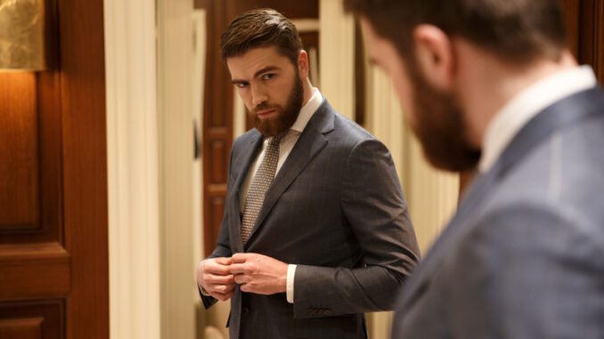 View from back of handsome bearded man looking at the mirror while being in a shop
